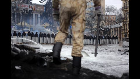 A protester stands on top of barricades in Kiev on Tuesday, January 28.