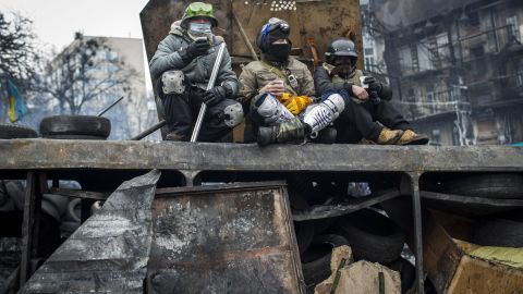 Anti-government protestors sit on the wreckage of a bus, used as a barricade on Grushevskogo Street, on January 28, 2014 in Kiev, Ukraine.