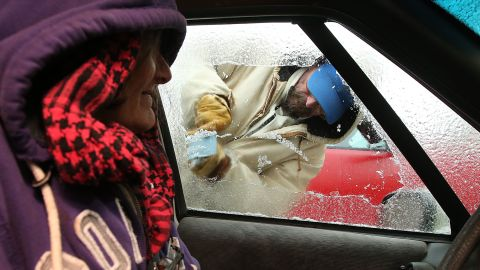 Sue Morrison watches as Chris McAdams scrapes ice from her car on January 29 in Panama City Beach, Florida.
