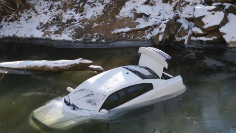 A car lies half submerged in the Cahaba River in Mountain Brook, Alabama, on Thursday, January 30. The driver was able to escape before the car slid into the river during a snow storm on Tuesday and was not injured.