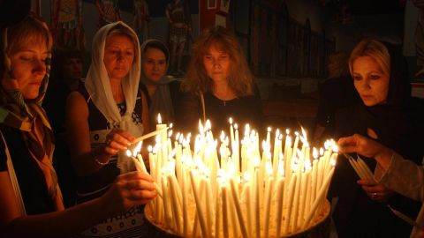 Russian women light candles after a special memorial service at a church on September 7, 2004.