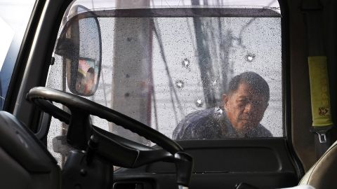 An anti-government protester inspects bullet holes in a window of his comrade's truck.