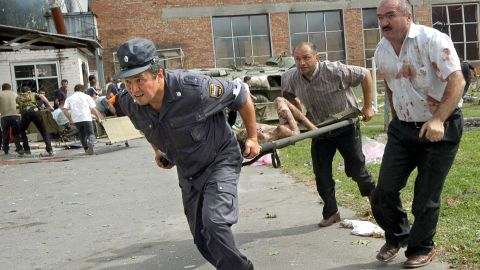 An Ossetian policeman and volunteers carry a stretcher with injured schoolgirl during the rescue operation.