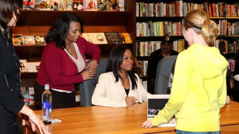 American gymnast Gabby Douglas signs autographs while her mother, Natalie Hawkins, stands nearby at a Skokie, Illinois, bookstore in 2013.