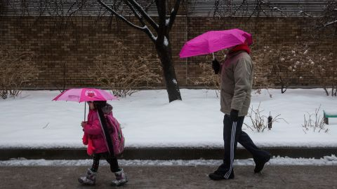 A man and a girl walk down a street February 5 in the Greenwich Village neighborhood of New York City.