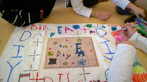 Three students, including one wearing Google Glass, work together after school to decorate the DIY Maker Club flag. A second-grader used Glass to shoot photos and videos and document the flag's creation.