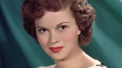 circa 1955: Headshot studio portrait of American actor Shirley Temple, in front of a green backdrop, wearing a short sleeve white blouse with a colored bows pattern and a pearl necklace. (Photo by Hulton Archive/Getty Images)