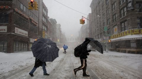 People walk through snow February 13 in the Chinatown neighborhood of New York City.