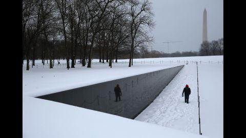 A man walks along the snow-covered Vietnam Veterans Memorial in Washington on February 13.