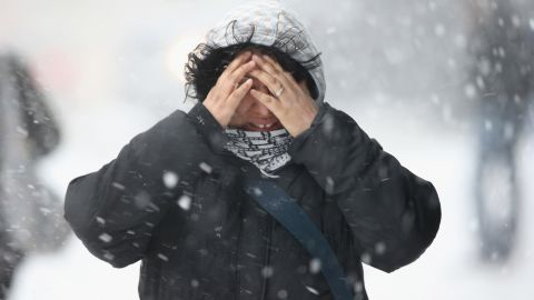 A woman covers her face while walking in New York City on February 13.