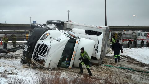 Rescue workers in Oxon Hill, Maryland, attempt to upright an overturned tractor-trailer on Interstate 495 on February 13.