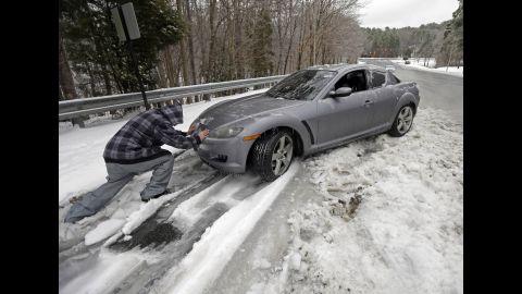 A man helps push a car in Chapel Hill, North Carolina, on February 13.