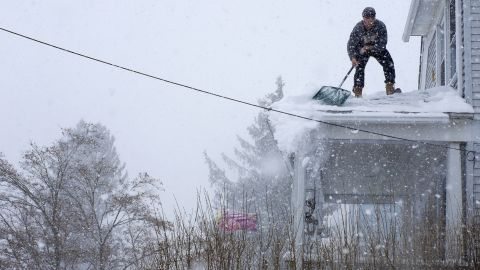 Chris Starace works to clear snow from his roof in Ossining, New York, on Thursday, February 13.
