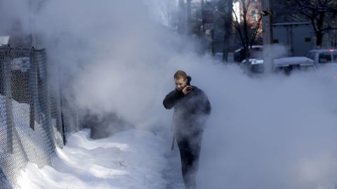 A pedestrian walks through a cloud of steam on a snowy street in New York on February 14. Commuters faced slick roads after a winter storm brought snow and ice to the East Coast.