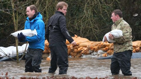 DATCHET, UNITED KINGDOM - FEBRUARY 14: Prince William, Duke of Cambridge (L) catches a sandbag thrown by his brother Prince Harry as they help soldiers build a flood defence wall at Eton End School on February 14, 2014 in Datchet, England. Flood water has remained high in some areas and high winds are causing disruption to other parts of the UK with the Met Office issuing a red weather warning. (Photo by Peter Macdiarmid/Getty Images)