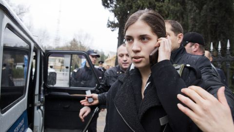 Nadezhda Tolokonnikova from the band Pussy Riot  is escorted to a police car after being detained in the Adler district of Sochi, on February 18, 2014.