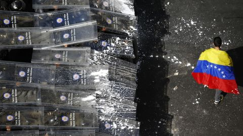 A protester walks past a line of riot police in Caracas on February 12.