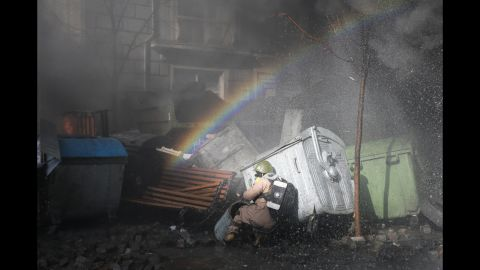 A rainbow forms over a protester ducking for cover in Kiev on February 18.