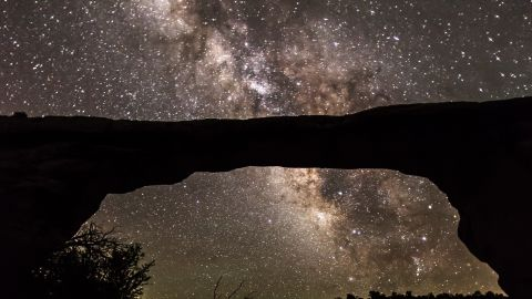 """<strong>Natural Bridges National Monument (Utah): </strong>The natural Owachomo Bridge in Utah is silhouetted against the Milky Way and thousands of stars. This photo was taken on a particularly clear night after a storm, and features potholes full of water reflecting the scene, says photographer <a href=""""http://jwfrank.com"""" target=""""_blank"""" target=""""_blank"""">Jacob Frank</a>."""
