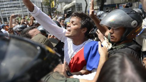 Leopoldo Lopez is escorted by members of the Venezuelan National Guard on Tuesday, February 18, after turning himself in to authorities.