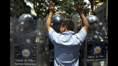 A protester faces riot police February 18 during a march in Caracas.