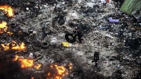 A protester rolls a tire toward burning barricades on February 20.
