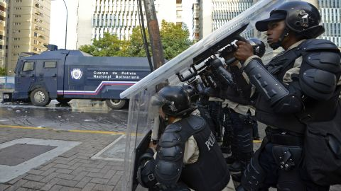 Members of the National Police protect themselves during a protest in Caracas on February 19.