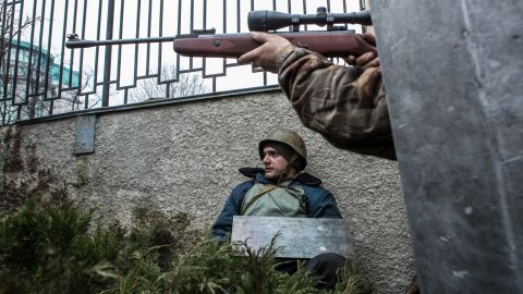 A protester aims a gun in the direction of suspected sniper fire in Kiev on Thursday, February 20. Thousands of demonstrators had packed Independence Square since November when President Viktor Yanukovych reversed a decision on a trade deal with the European Union and instead turned toward Russia.