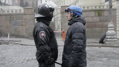 A high-ranking police officer, left, and a representative for the protesters speak with each other near the Cabinet of Ministers in Kiev on February 20.