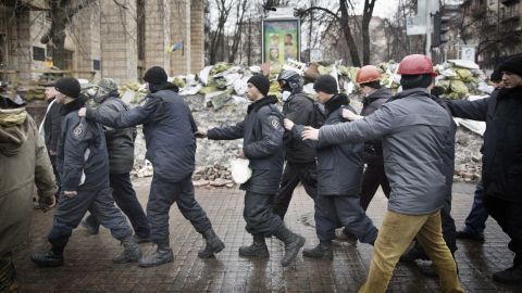 Captured police officers are led away by protesters in Kiev on February 20.