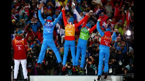 Gold medalists Anton Shipulin, Dmitry Malyshko, Evgeny Ustyugov and Alexey Volkov of Russia celebrate on the podium during the medal ceremony for the men's 4x7.5-kilometer relay.
