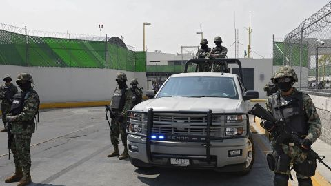 Marines stand guard as Guzman is presented to the press.