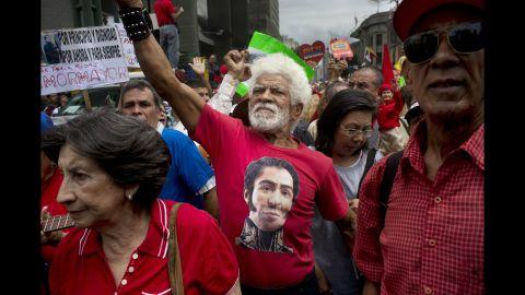 A man wearing a T-shirt with the likeness of Latin American hero Simon Bolivar joins in a pro-government march in Caracas on Sunday, February 23.
