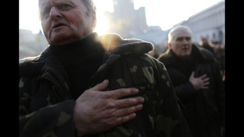 People sing the Ukrainian national anthem at Independence Square on Monday, February 24.