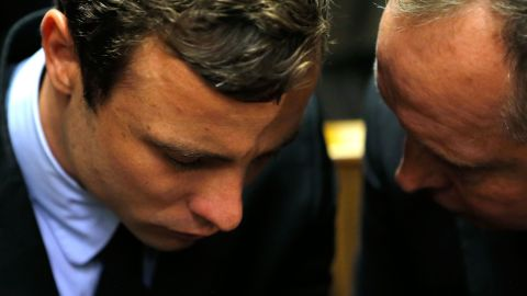 Oscar Pistorius (L) speaks with his lawyer Kenny Oldwage prior to an indictment hearing on August 19, 2013 in Pretoria, South Africa.