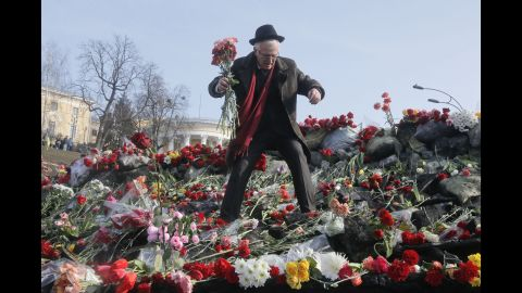 A man places flowers at a barricade near Independence Square on February 26.