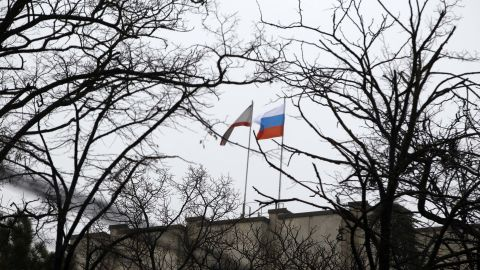 SIMFEROPOL, UKRAINE - FEBRUARY 27: Russian flag is raised at the parliament building after two different groups of around 60 armed men raided and occupied the regional government and parliament buildings in Simferopol, the capital of the Autonomous Republic of Crimea on February 27, 2014. Police forces take tightened security measures in front of the parliament building. (Photo by Bulent Doruk/Anadolu Agency/Getty Images)