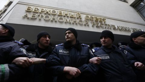 Security forces stand guard during clashes between opposing sides in front of Crimea's parliament building in Simferopol on February 26.