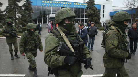 Armed men patrol outside the Simferopol International Airport on Friday, February 28.