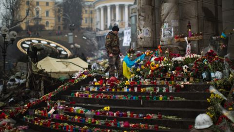 A protester stands at a memorial March 1 for the people killed in clashes at Independence Square.