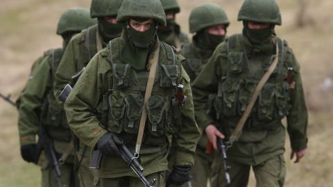 Soldiers who were among several hundred that took up positions around a Ukrainian military base walk on the base's periphery in Crimea on March 2, 2014 in Perevanie, Ukraine. Several hundred heavily-armed soldiers not displaying any idenifying insignia took up positions outside the base and parked several dozen vehicles, mostly trucks and patrol cars, nearby. The new government of Ukraine has appealed to the United Nations Security Council for help against growing Russian intervention in Crimea, where thousands of Russian troops reportedly arrived in recent days at Russian military bases there and also occupy key government and other installations. World leaders are scrambling to persuade Russian President Vladimir Putin to refrain from further escalation in Ukraine. Ukraine has put its armed forces on combat alert.