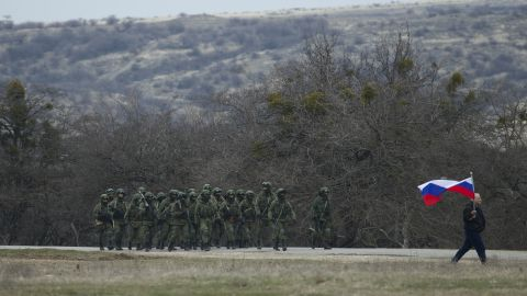 Soldiers walk outside a Ukrainian military base in Perevalne as a local resident waves a Russian flag March 2.