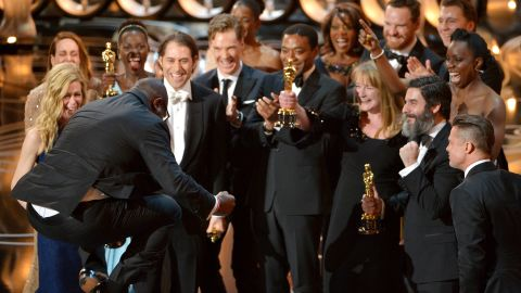 """Director Steve McQueen, left, celebrates with the cast and crew of """"12 Years a Slave"""" as they accept the Academy Award for best picture on Sunday, March 2."""