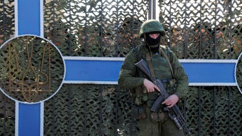 Ukrainian soldier stands behind a fence while unidentified armed men block the headquarters of the Ukrainian Navy in Sevastopol on March 3, 2014. The Russian Black Sea Fleet commander Aleksandr Vitko has issued an ultimatum to the Ukrainian military personnel in Crimea, the Interfax-Ukraine news agency reported. Ukraine accused Russia on Monday of pouring more troops into Crimea as world leaders grappled with Europe's worst standoff since the Cold War and the Moscow market plunged on fears of an all-out conflict. AFP PHOTO/ VIKTOR DRACHEV (Photo credit should read VIKTOR DRACHEV/AFP/Getty Images)