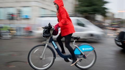 "A cyclist rides a public hire ""Boris Bike"" in central London, November 2013."