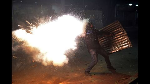 A protester tries to throw a homemade bomb during clashes with police March 3 in Caracas.