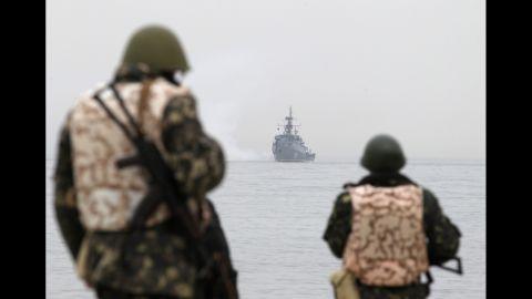Ukrainian troops watch as a Russian navy ship blocks the entrance of the Ukrainian navy base in Sevastopol on March 4.