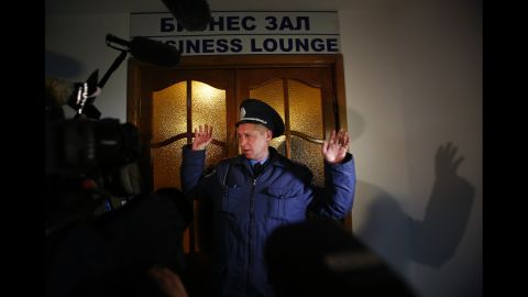 A Ukrainian police officer gives instructions to members of the media in front of the business class lounge of the Simferopol airport on March 5.