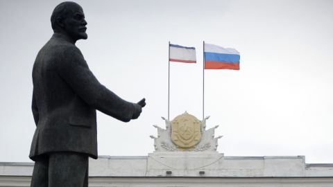 Russian (R) and Crimean flags flutter on top of the Crimean government building near a statue of Vladimir Lenin in Simferopol on March 4, 2014. Fears of an assault by Russian forces on Ukrainian military bases surrounded in Crimea did not materialise overnight, a Ukrainian defence ministry spokesman said Tuesday. 'The night was quiet,' Vladyslav Seleznyov, the defence ministry spokesman for Crimea, told AFP in the regional capital Simferopol. AFP PHOTO / ALEXANDER NEMENOV (Photo credit should read ALEXANDER NEMENOV/AFP/Getty Images)
