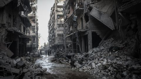 Syrians inspect the rubble of destroyed buildings in Aleppo following a reported airstrike by Syrian government forces on Friday, March 7.